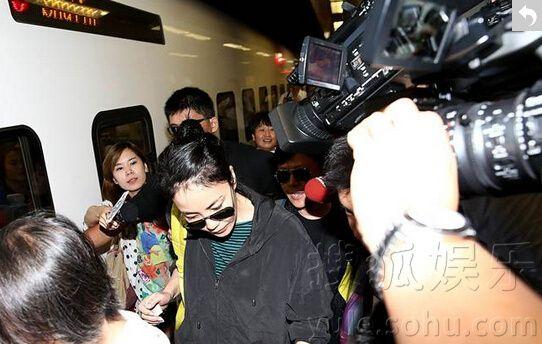 王菲拍完广告搭动车回台北遭媒体围追低头快走(图)